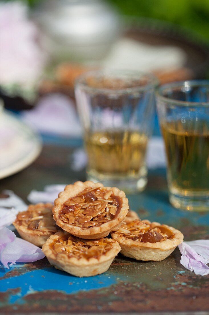 Almond tarts and glasses of tea on old metal chair