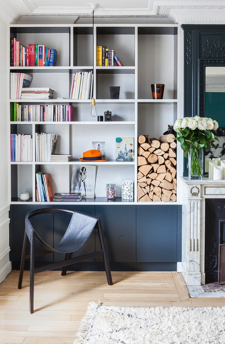 Fitted shelves and black designer chair next to fireplace