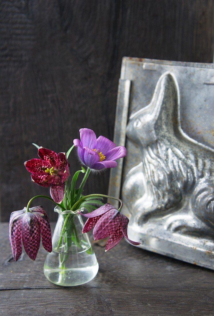 Schachbrettblumen und eine Kuhschelle vor einer alten Backform
