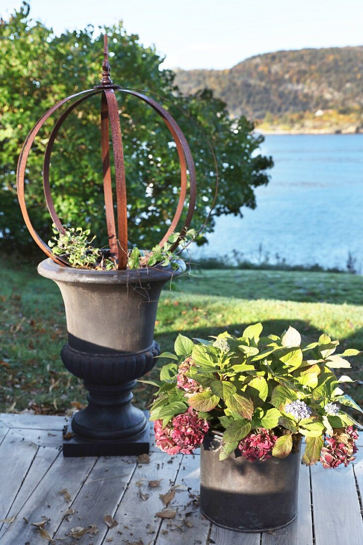 Sculpture in planted urn next to potted hydrangea on wooden terrace