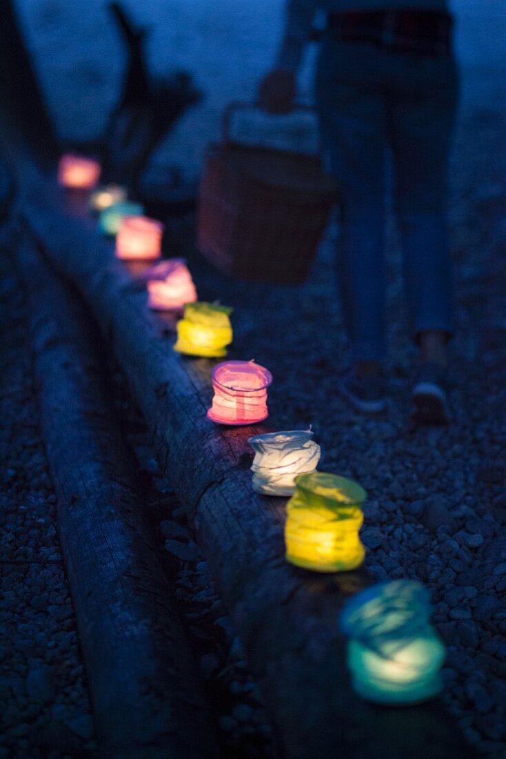 Lanterns on horizontal tree trunk next to river