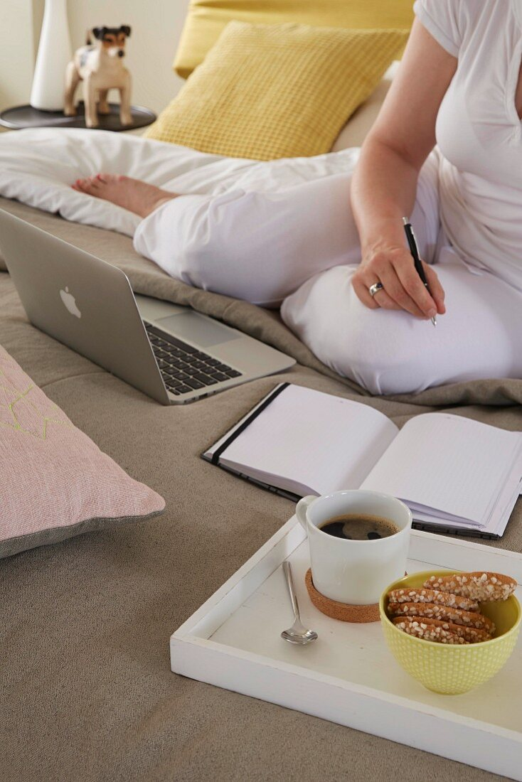 A woman with a breakfast tray working on a bed