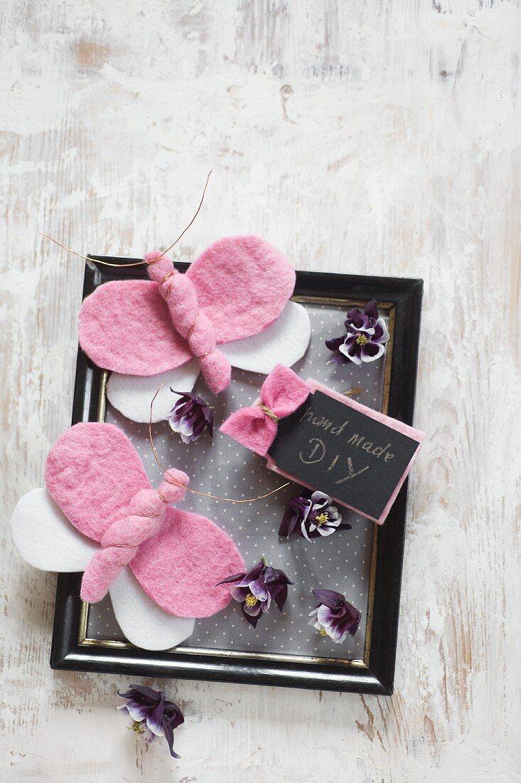 DIY Schildchen und Schmetterlinge aus rosa Filz auf schwarzem Bilderrahmen mit violetten Blüten