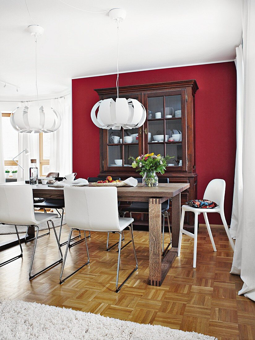 White, leather-covered bucket chairs around an oak dining table opposite a buffet against a Bordeaux red wall