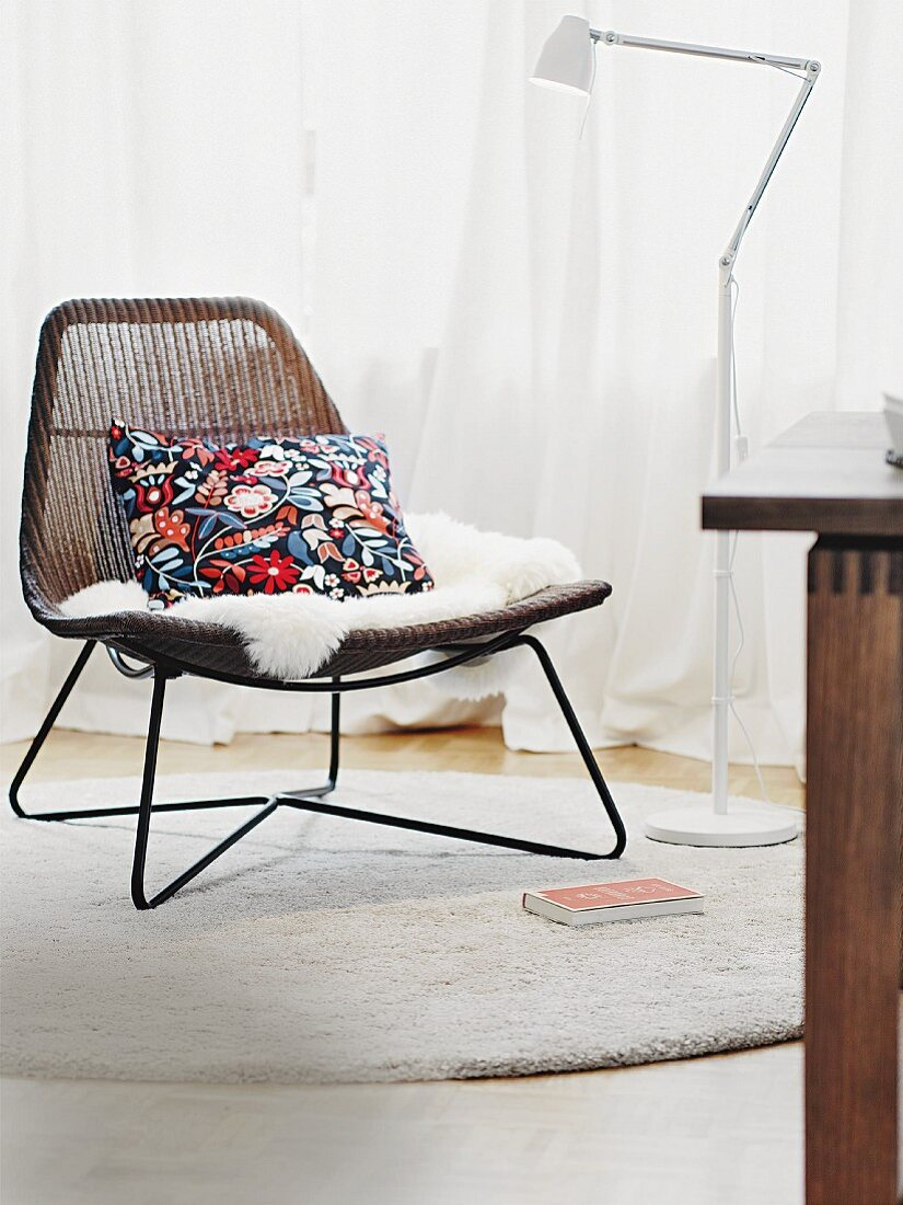 A wicker chair with fur and a floral patterned cushion, next to a white floor lamp in front of a window