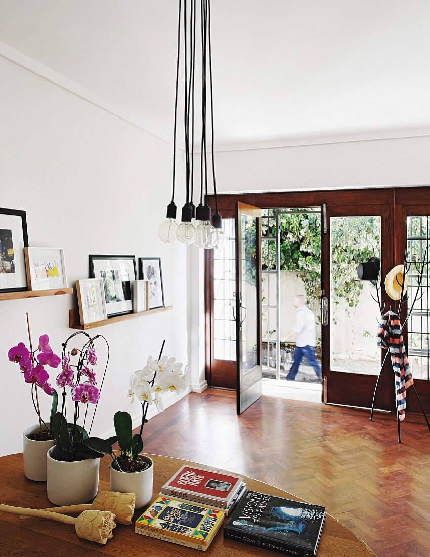 Coat stand on exotic-wood parquet floor and framed pictures on narrow shelves in elegant foyer