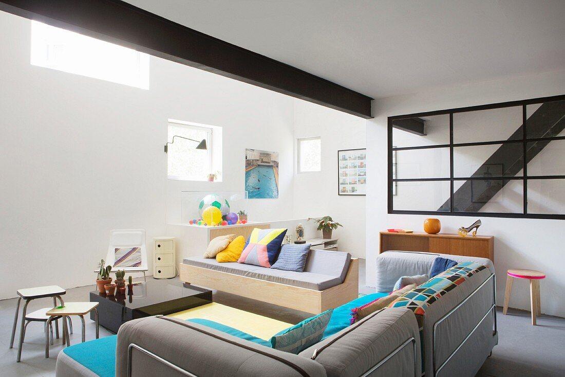 Black steel girder below mezzanine in cosy eclectic living area