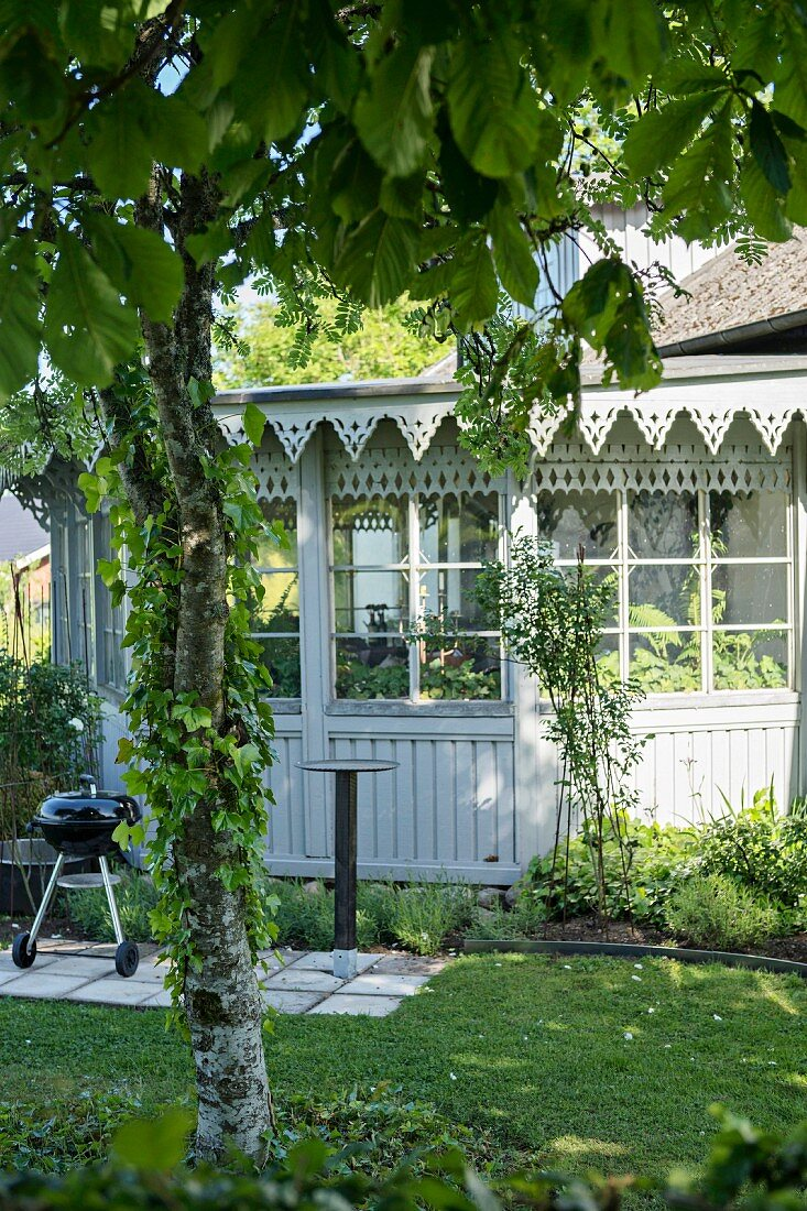 Terrace in garden outside traditional conservatory with ornate wooden eaves and lattice windows