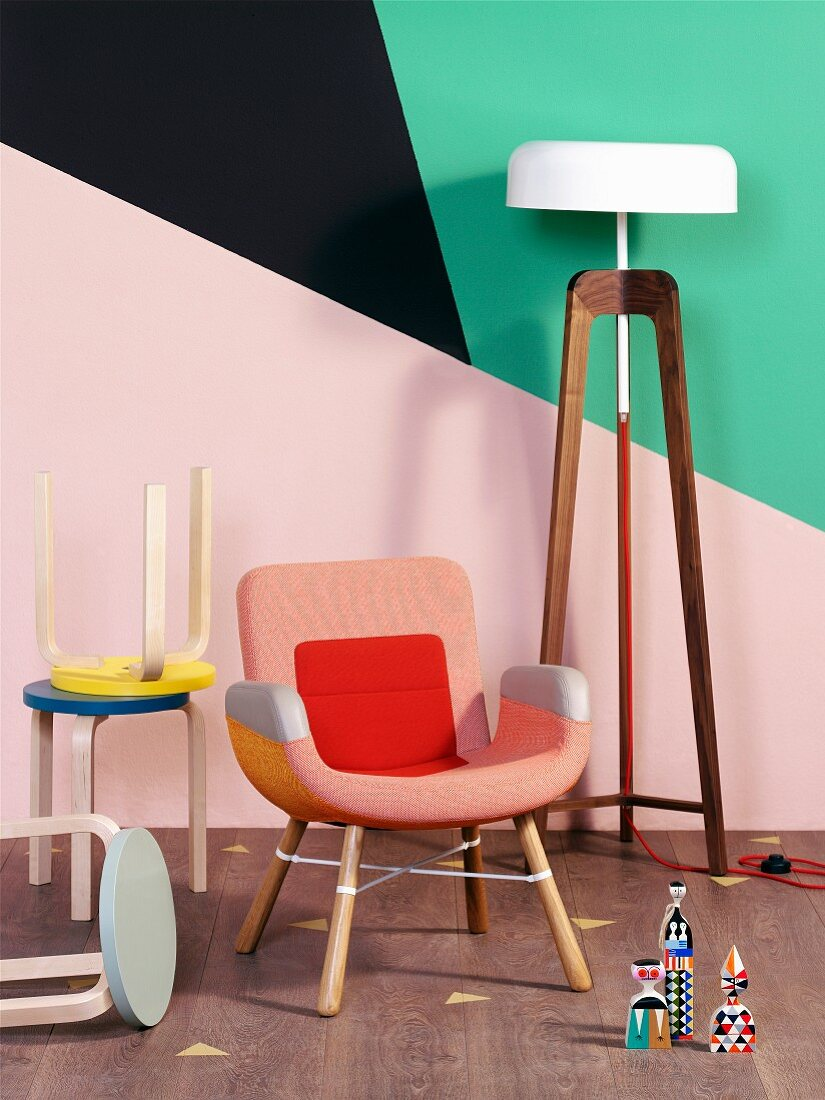 Collection of stools and armchair next to standard lamp against wall with geometric pattern of bright colours