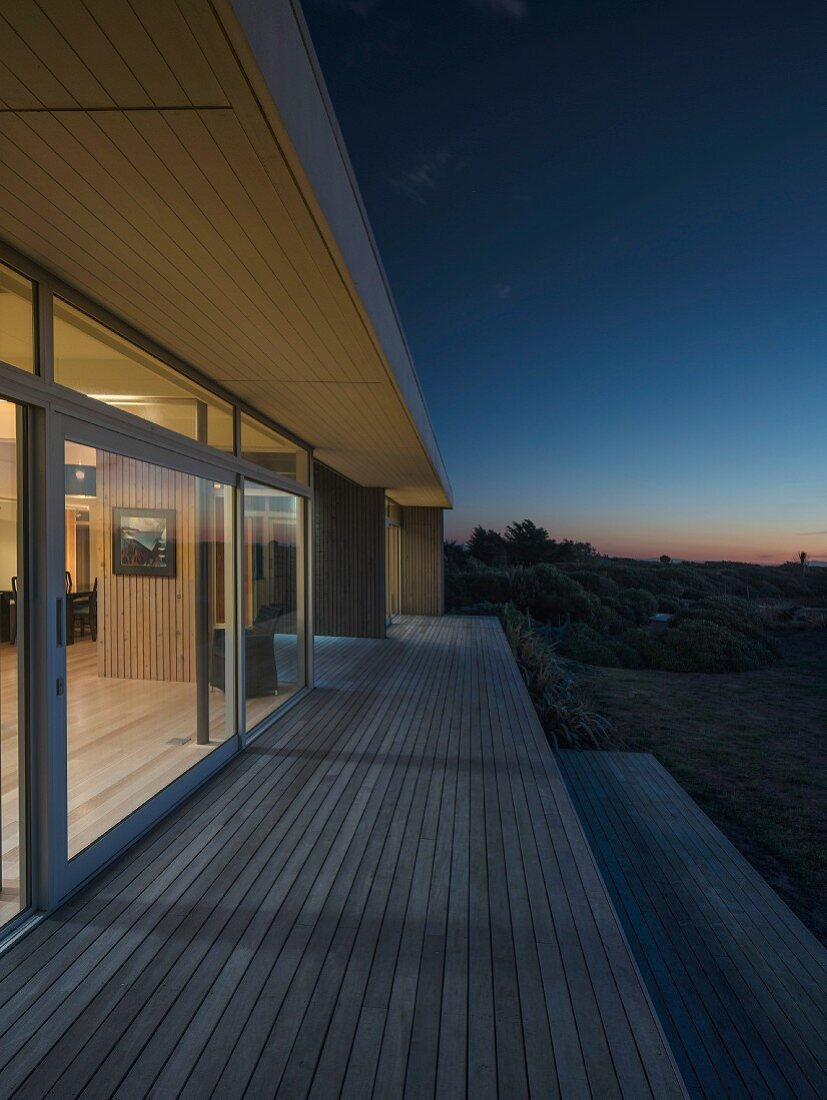 Wooden deck outside contemporary house with illuminated interior at twilight