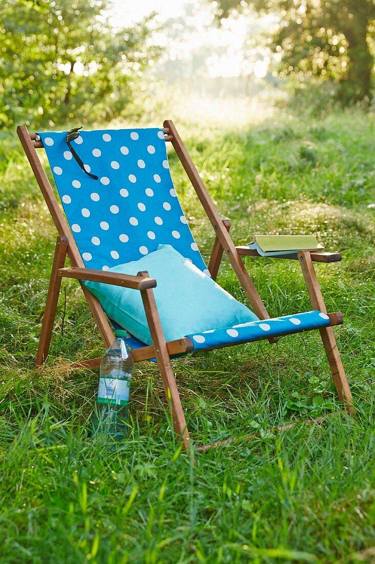 A deckchair with homemade fabric cover on green grass in a garden