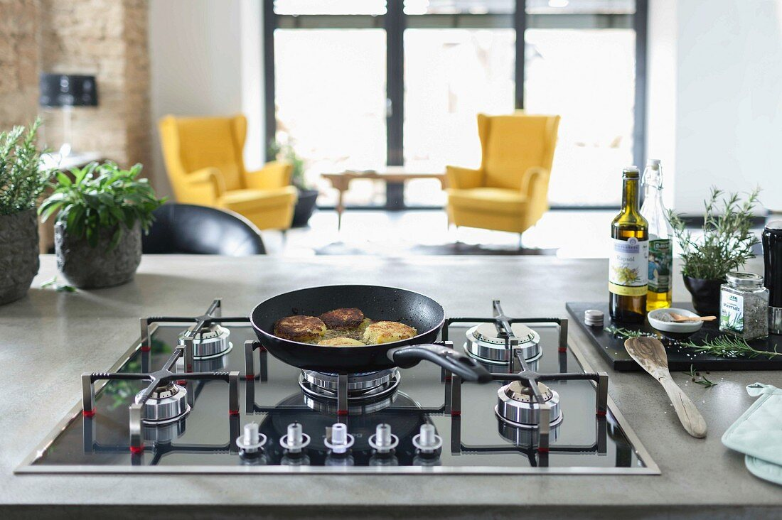 A kitchen island with a concrete work surface and a gas hob with a pt burger in a pan