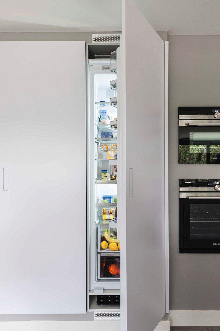A built-in, floor-to-ceiling cupboard with an open fridge door