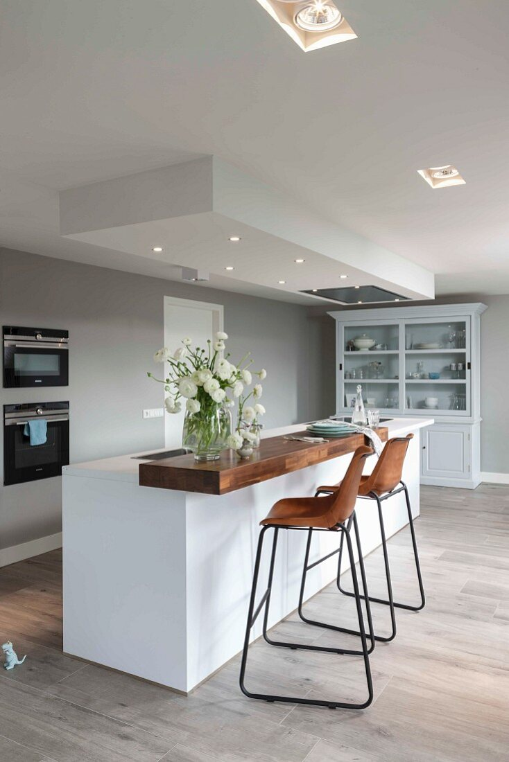 A modern kitchen in white with built in spot lights in a suspended ceiling with bar stools with wooden seats and metal frames in front of an island bar