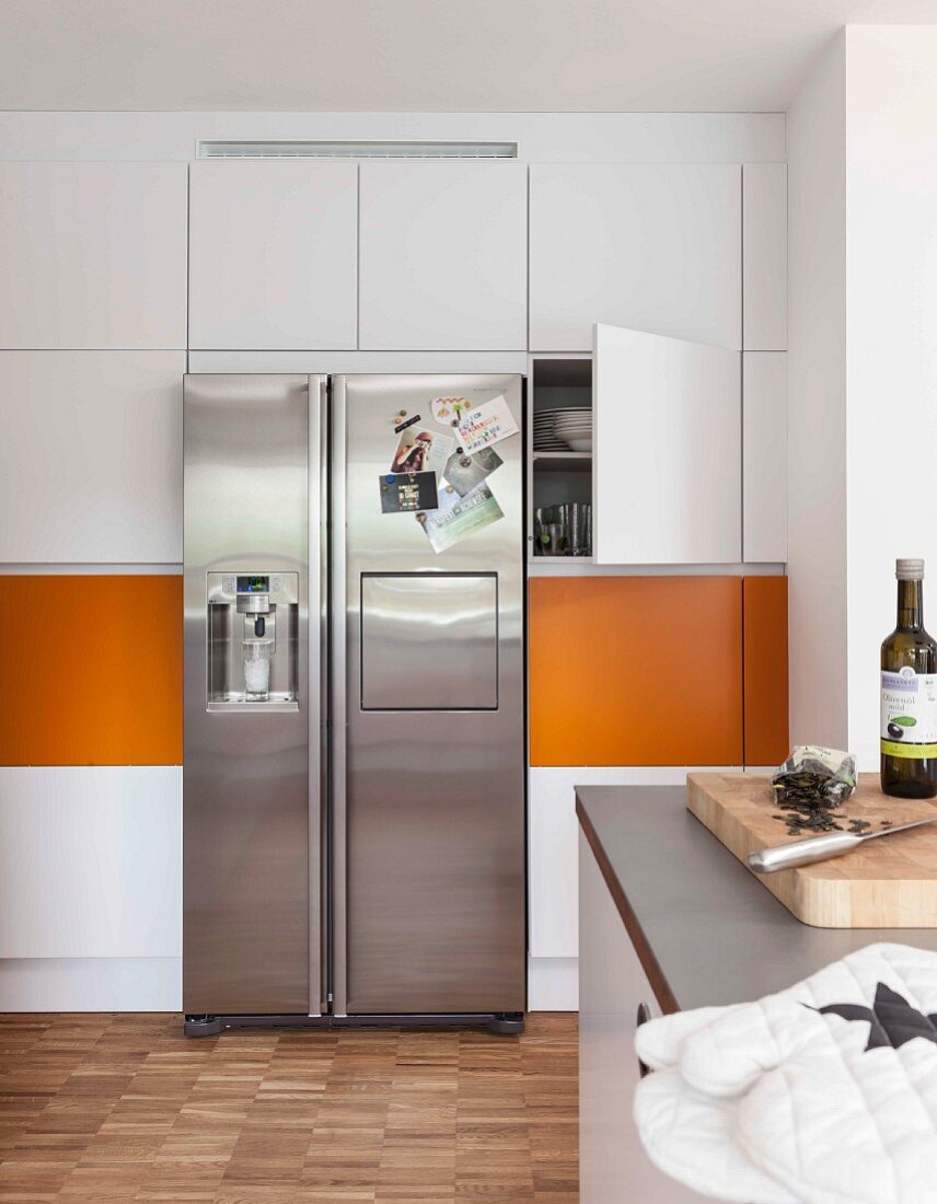 Built-in cupboards with orange panels and a stainless steel fridge-freezer combination