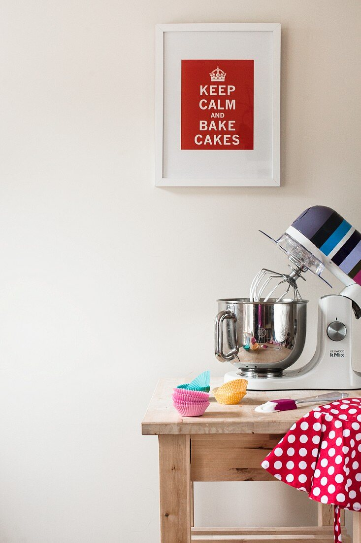 Mixer and baking utensils on a wooden kitchen table