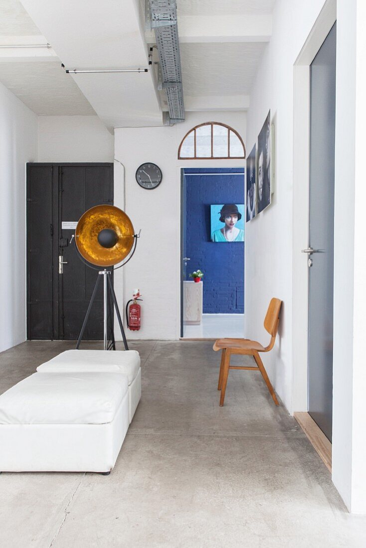White pouffes and doors in industrial-style foyer