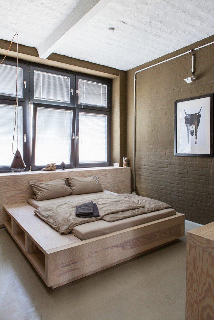 Double bed below window in minimalist beige bedroom