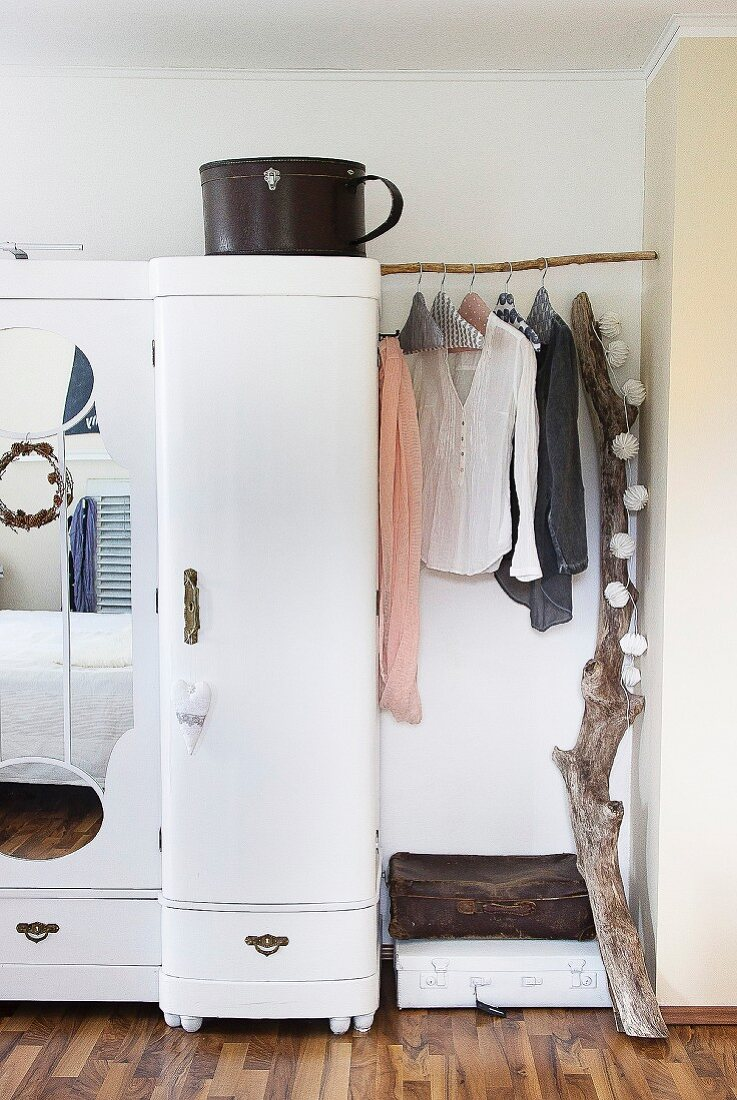 Clothing on fabric-covered coathangers on branch used as clothes rack