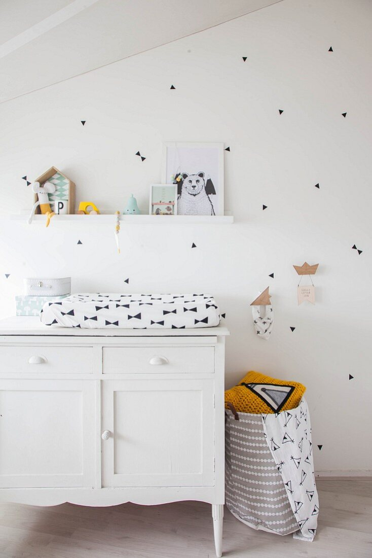 Changing mat on top of white cabinet against white wall decorated with black stickers