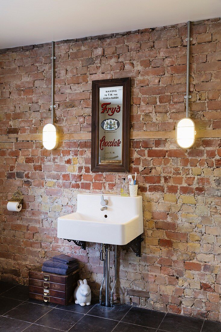 Sink mounted on unrendered brick wall
