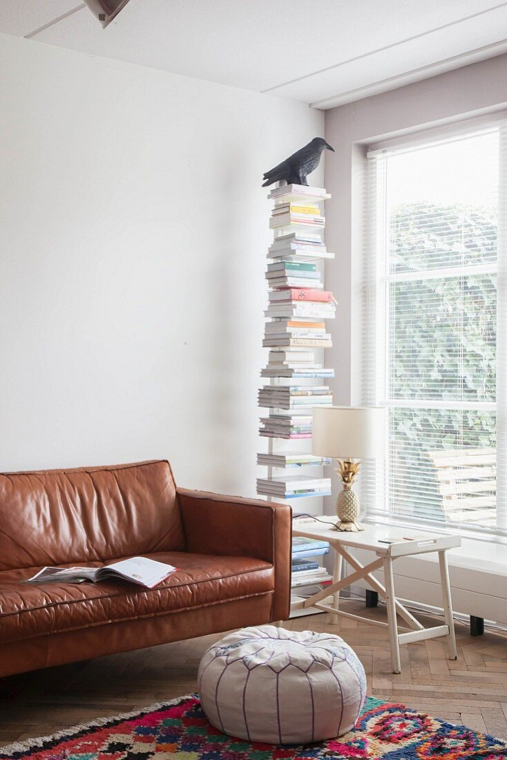 Pouffe and leather couch next to bookstand and table lamp on tray table in reading corner