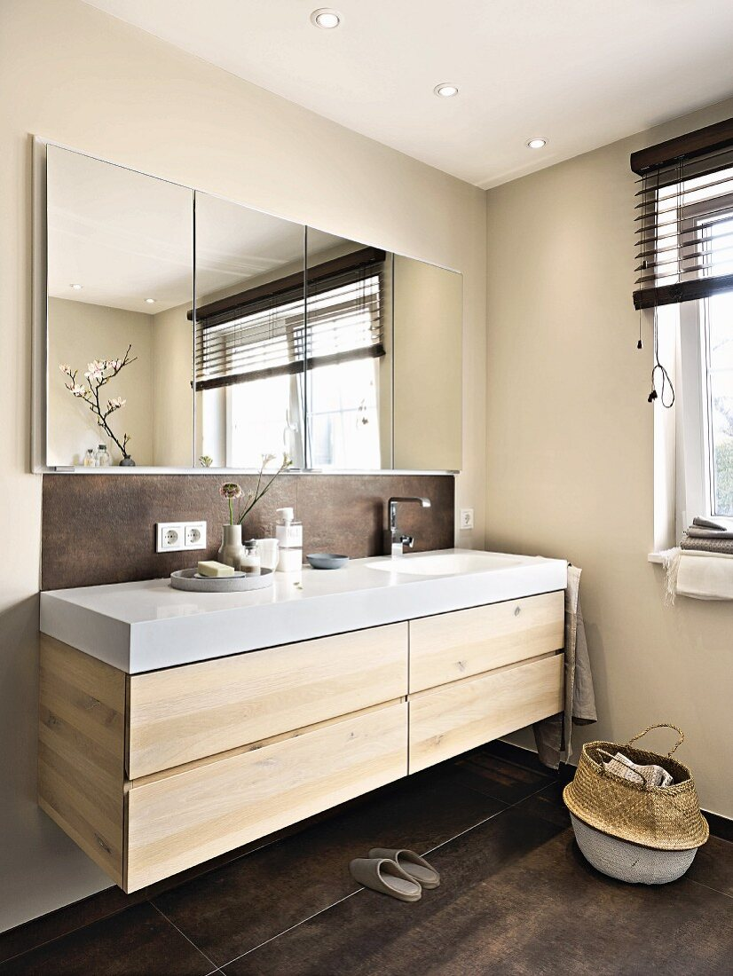 A sink unit made of light wild oak with a shower cabient inset in the wall in an elegant bathroom