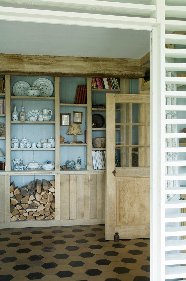 Glasses, books and firewood on fitted shelves in renovated country house