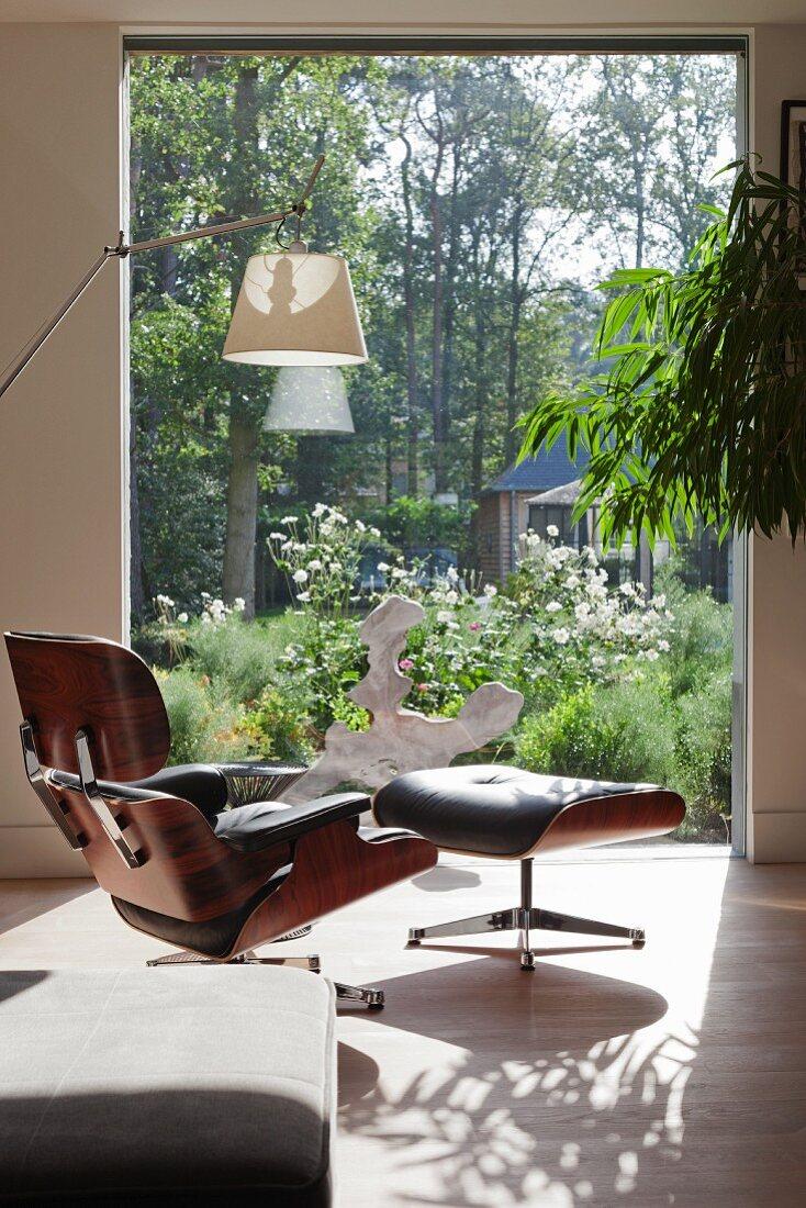 View past designer armchair through window and into garden