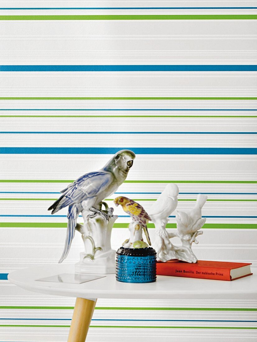 A side table with bird ornaments in front of green and blue striped non-woven wallpaper