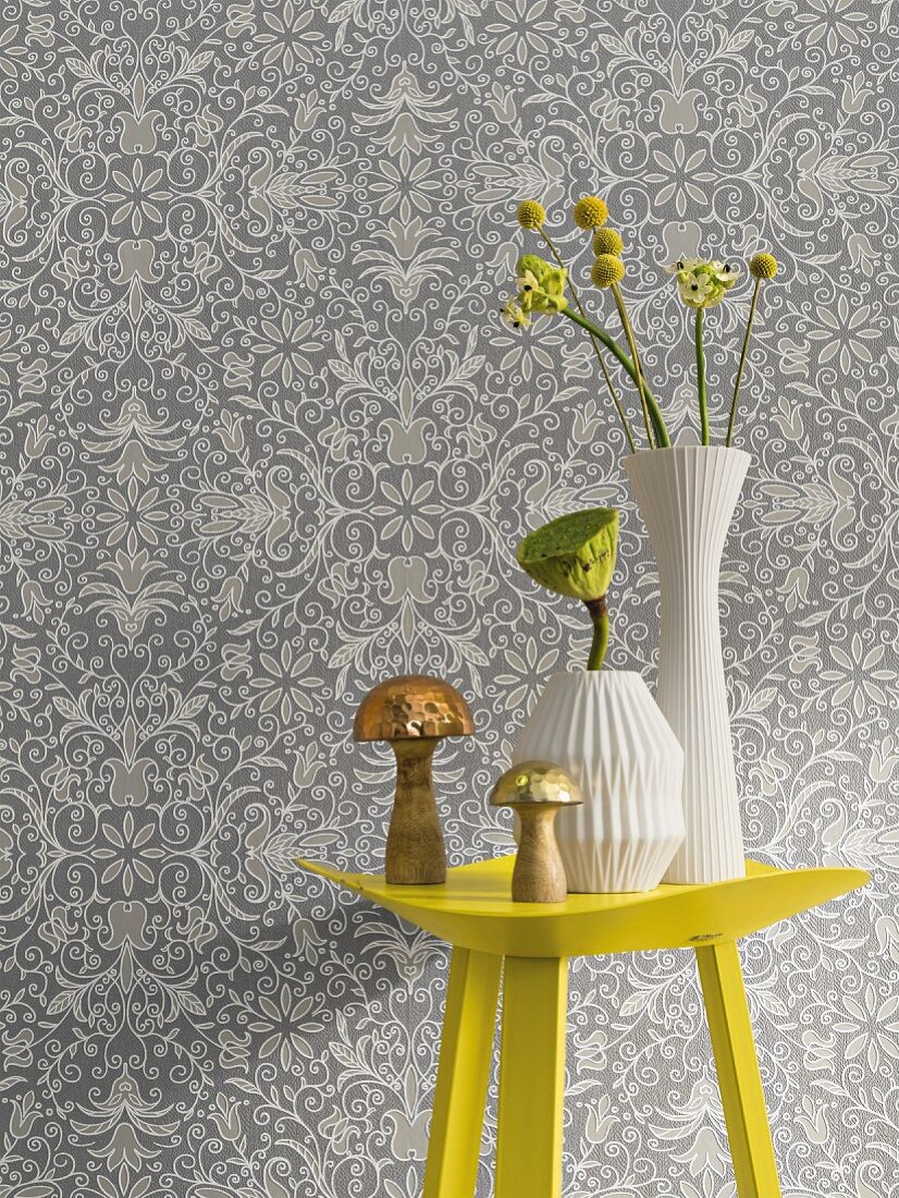 A yellow metal table with vases in front of non-woven wallpaper with a floral pattern in shades of grey