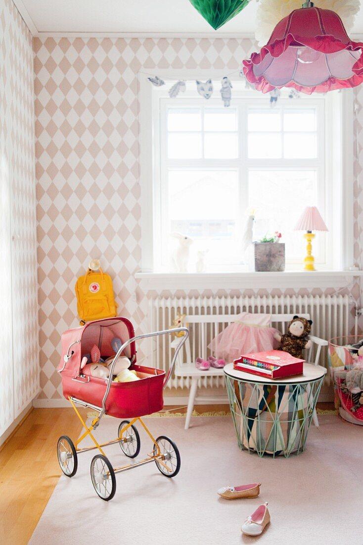 Mädchenzimmer mit Rautenmuster-Tapete und rotem Retro Puppenwagen