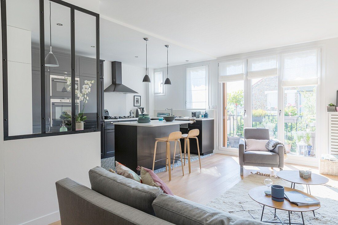 Glass partition, black fitted kitchen and island counter in open-plan living space