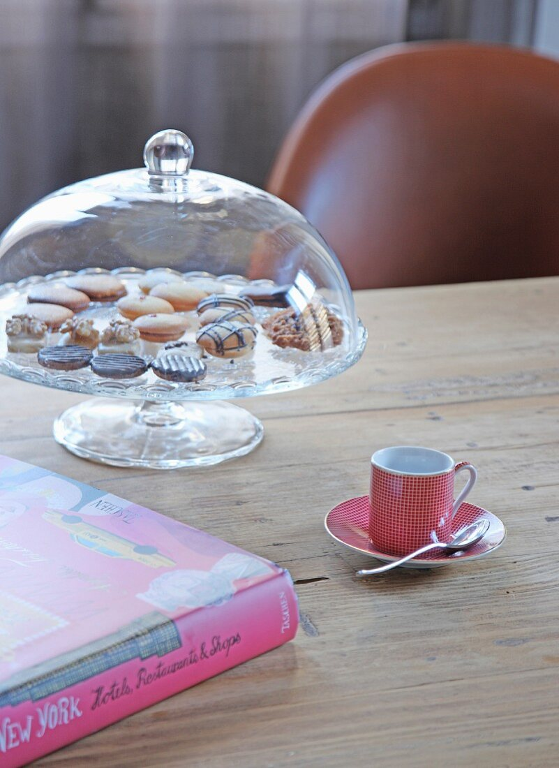 Cake stand under glass cover, cup and book on wooden table