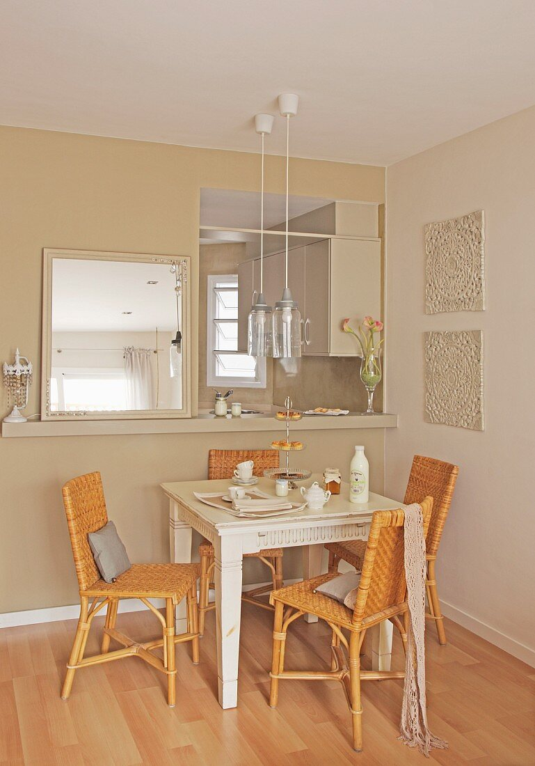 Dining table and cane chairs below serving hatch leading to kitchen