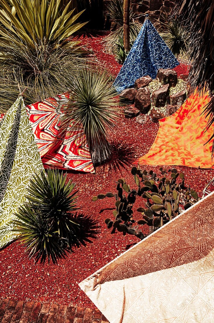 Different patterned towels in the red sand between plants