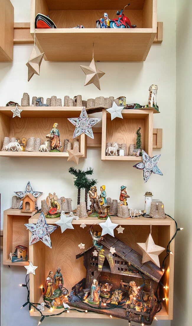 Christmas decorations and nativity scene in wooden boxes on wall