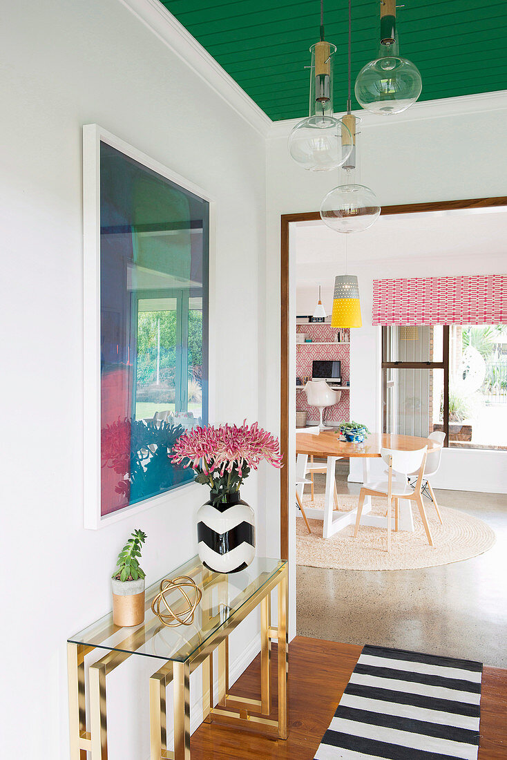 View from the hallway with a golden console table into the dining room