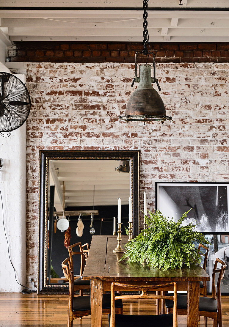 Fern on the dining table in the loft with brick wall and industrial lamp