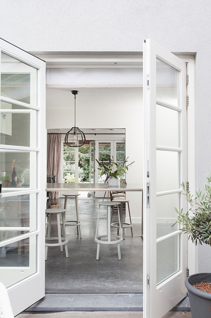 Dining table and stools seen though open terrace doors