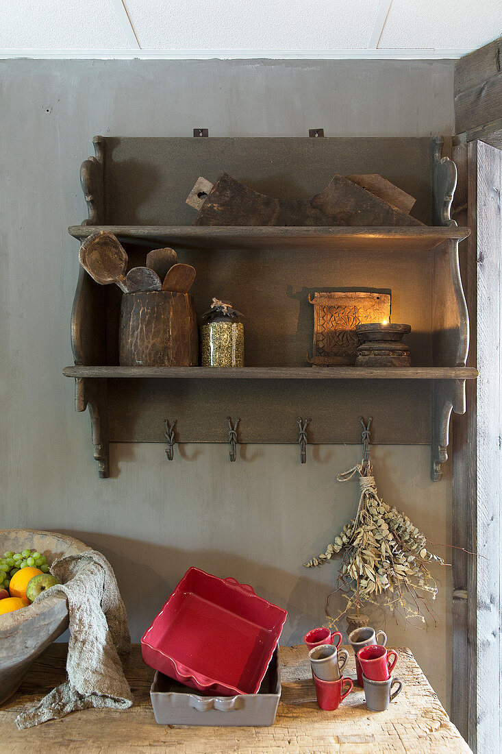 Red and grey baking trays and cups on worksurface below wall-mounted wooden shelves