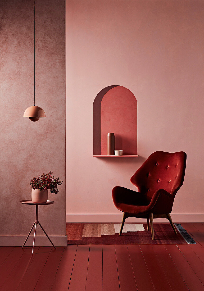 Red armchair in front of wall console, side table with house plants in front of room divider wall