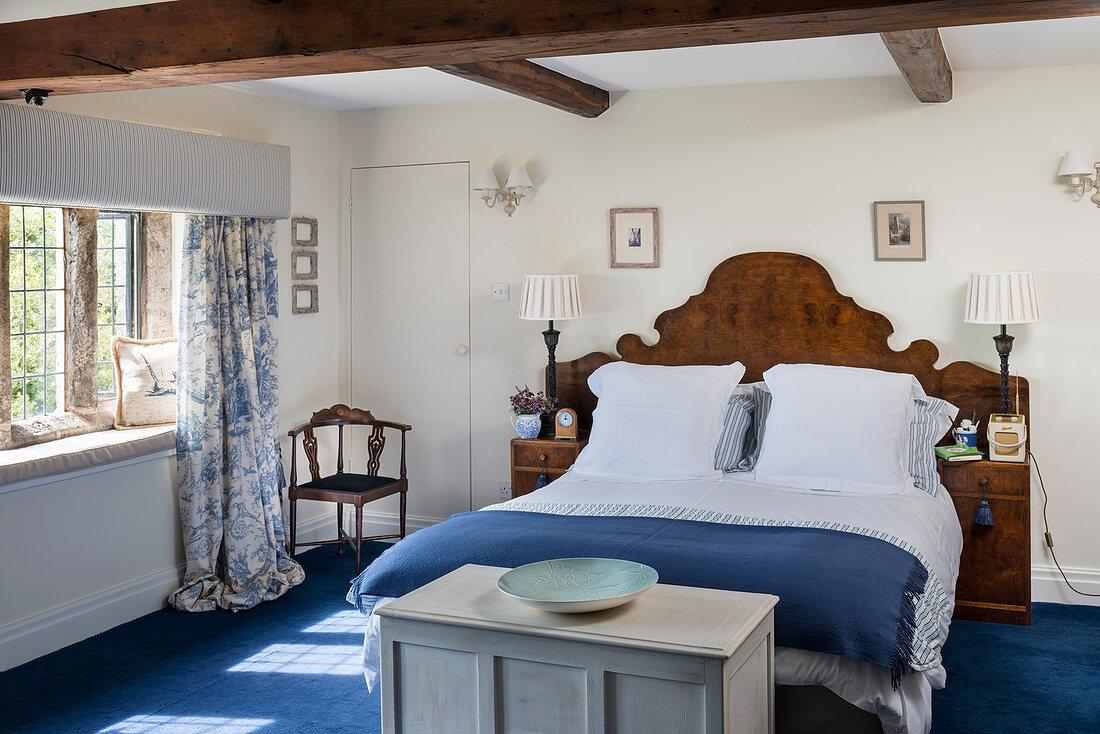 Doppelbett mit antikem Kopfteil aus Holz in weiß-blauem Schlafzimmer