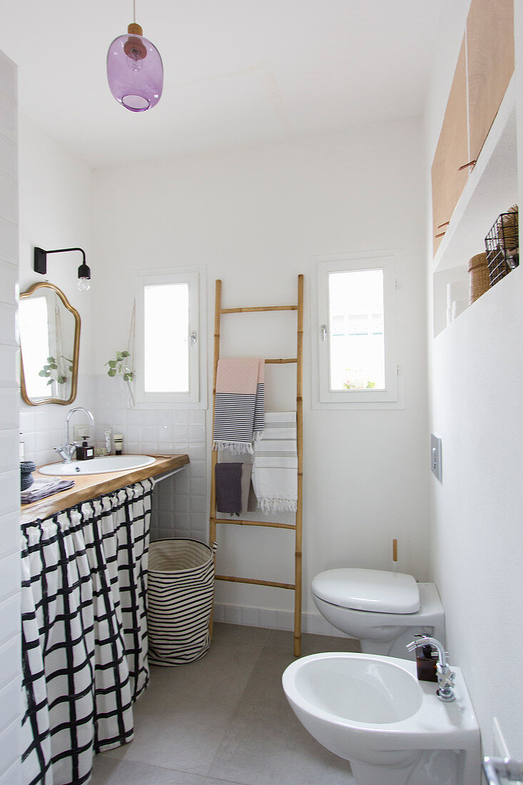 Eclectic bathroom with curtain below washstand, towel rail, toilet and bidet
