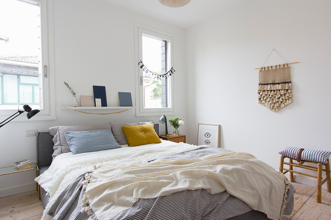 Schlafzimmer mit Doppelbett, Handarbeit an weißer Wand