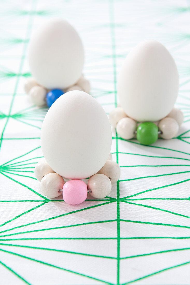 weiße Eier auf Kränzchen aus Holzperlen