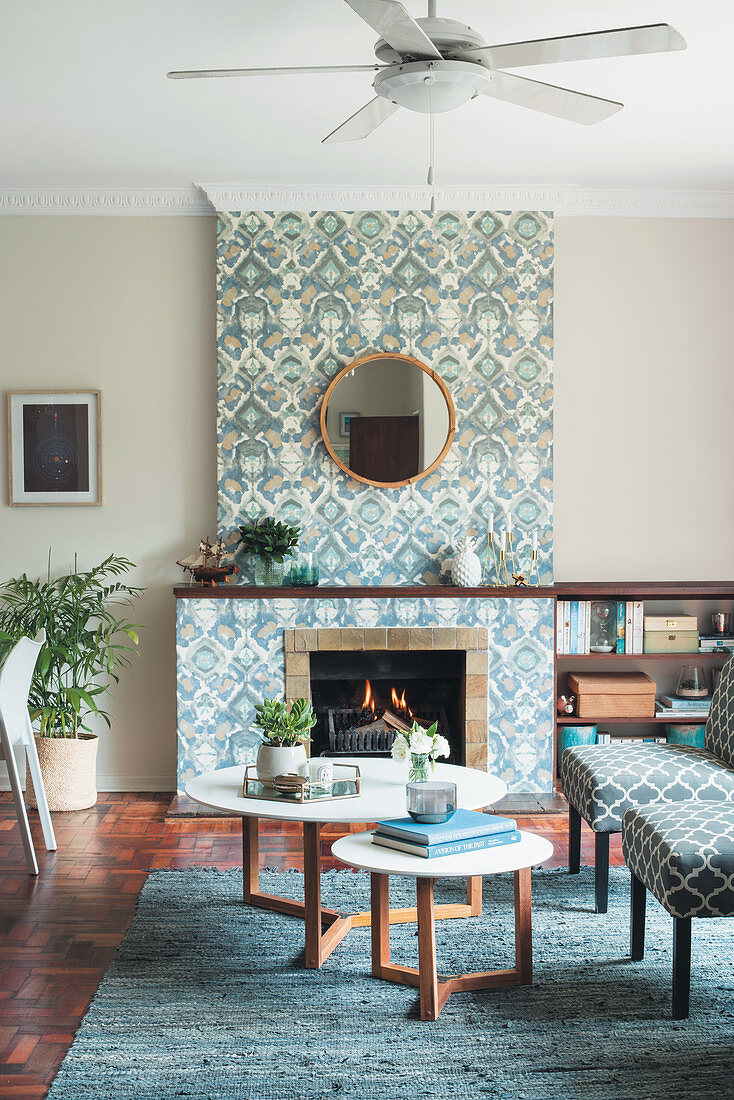 Patterned wallpaper on chimney breast and ceiling fan in living room
