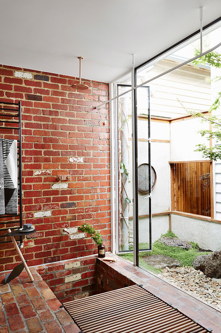 Shower with brick wall and garden access