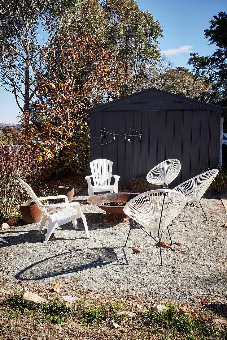 White chairs around fire bowl on terrace in autumn garden