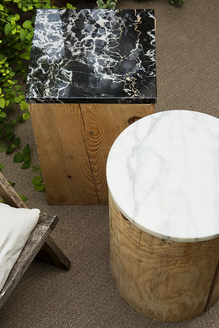Marble top on wooden block used as side table in garden